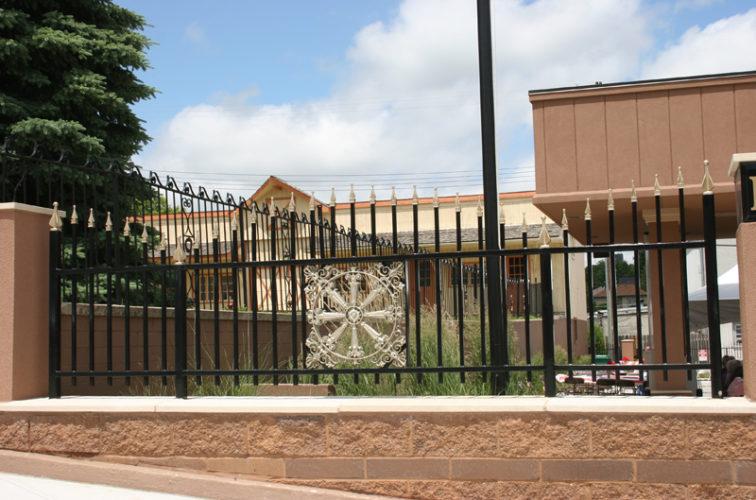 AFC Iowa City - Custom Iron Gate Fencing, 1229 Overscallop with quad flare & emblem