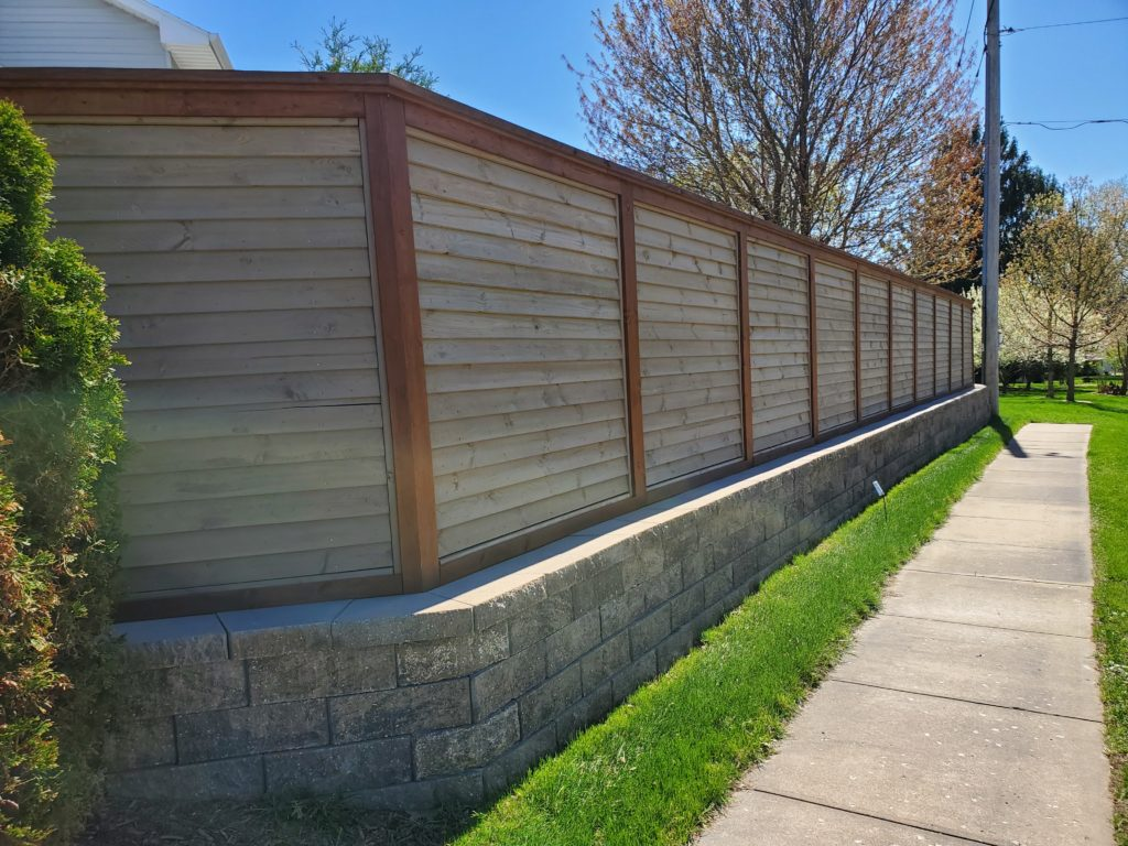 Residential steel louvered fence with wood fence posts and rails