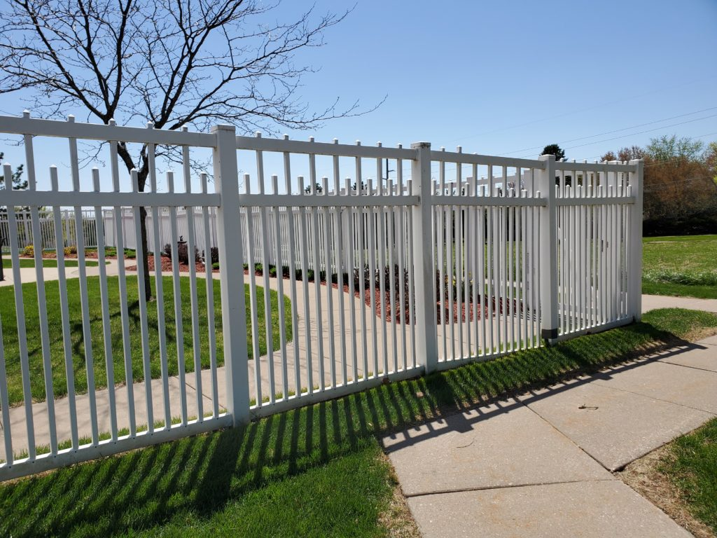 White ornamental iron fence in Iowa City with an alternating picket design